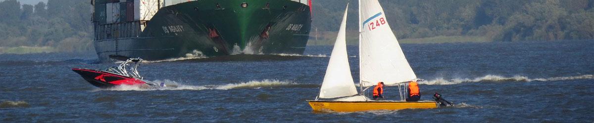 Ein Segelboot auf der Elbe und im Hintergrund nähert sich ein Frachtschiff