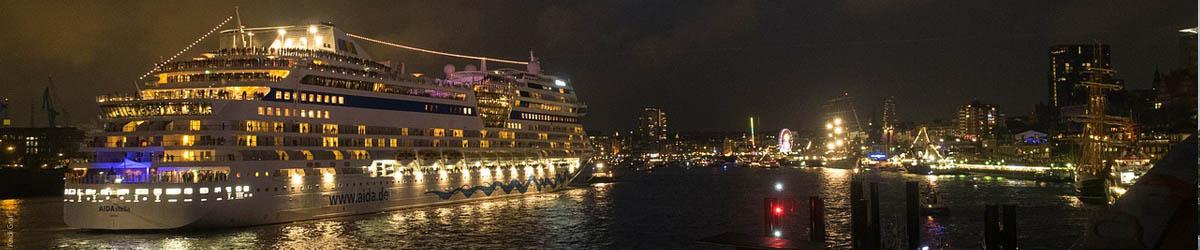 Ein AIDA Kreuzfahrtschiff verlässt den Hamburger Hafen in der Nacht