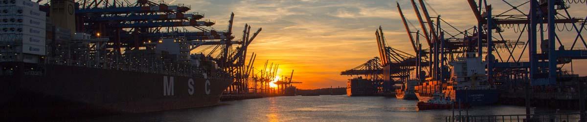 Sonnenuntergang im Containerhafen mit Kränen und einigen Schiffen - MSC
