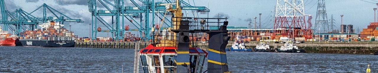Ein Schlepper vor der Kulisse eines Containerhafens - Hamburger Hafen