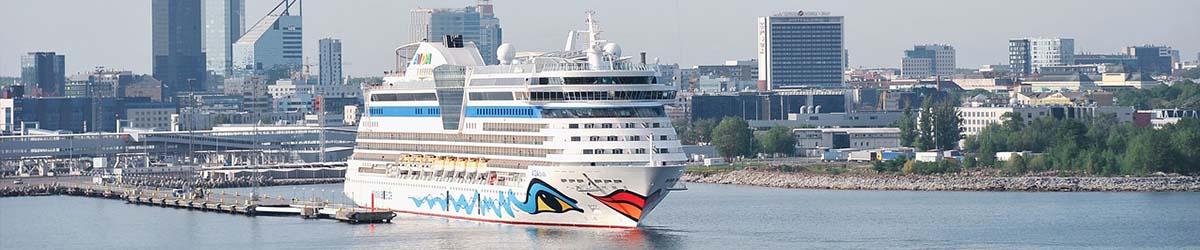 Ein AIDA Kreuzfahrtschiff liegt im Hafen an der Pier in einer großen Stadt.