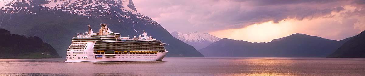 Kreuzfahrtschiff liegt in einem Fjord umringt von hohen schneebedeckten Bergen