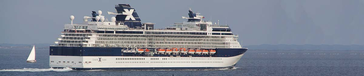 Kreuzfahrtschiff auf See mit Land in Sicht, im Hintergrund kreuzt ein Segelboot